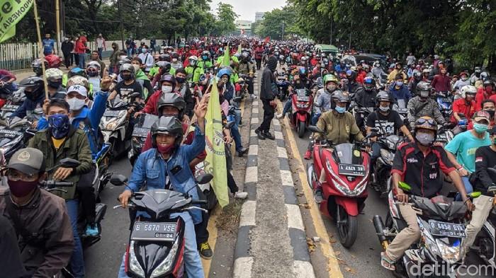 Polisi membuka blokade pagar betis di Jalan Daan Mogot Tangerang, Kamis (8/10). Alhasil, massa dari buruh dan pelajar mengalir ke arah Kalideres Jakarta Barat.