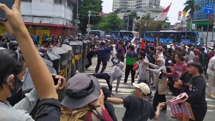 Massa demonstrasi UU Cipta Kerja melempari polisi dengan botol di Harmoni, Jakarta.