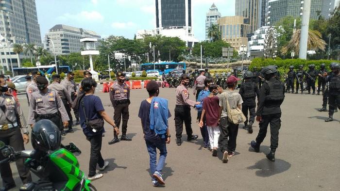 Pengamanan demo tolak UU Cipta Kerja di kawasan Patung Kuda Jakarta. 8 pemuda diamankan, masa buruh diminta bubar.