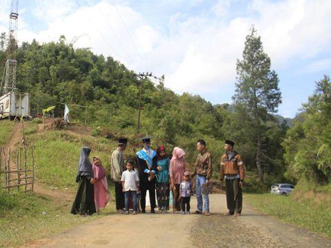 Potret Ahmad Krismon dan keluarganya yang naik ke atas bukit agar mendapatkan sinyal