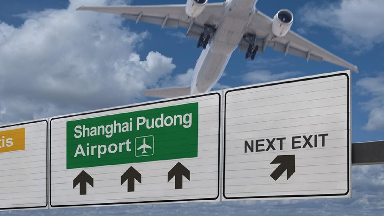 Road sign indicating the direction of Shanghai Pudong airport and a plane that just got up.