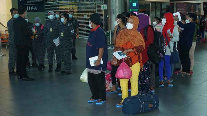 Sejumlah Pekerja Migran Indonesia (PMI) ilegal dalam proses pemulangan,  di Kuala Lumpur International Airport (KLIA) 2 dengan dikawal petugas Imigrasi Malaysia dan pejabat KBRI Kuala Lumpur, Sabtu (10/10/2020). Sebanyak 500 pekerja dipulangkan dengan tujuan Surabaya, Jakarta dan Medan karena masa tahanannya sudah habis. ANTARA Foto/Agus Setiawan/hp.