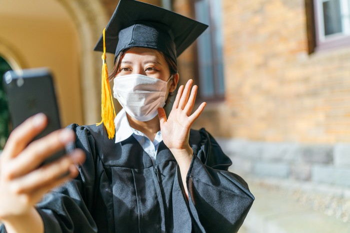A student in graduation gown is making a video call with a smart phone.