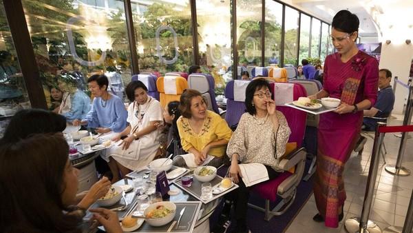 eorang pramugari menyajikan makanan di restoran bertema penerbangan di kantor pusat Thai Airways di Bangkok, Thailand.