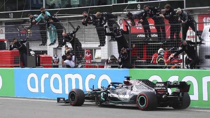 Mercedes driver Lewis Hamilton of Britain crosses the finish line to win the Eifel Formula One Grand Prix as team members celebrate at the Nuerburgring racetrack in Nuerburg, Germany, Sunday, Oct. 11, 2020. (AP Photo/Matthias Schrader, Pool)