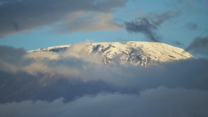 The snow covered peak of Mt. Kilimanjaro is seen from the Amboseli National Park June 21, 2018. - Amboseli is among the most renowned case studies in the world for elephant population and behavioural factors with the last official count of the perchyderms, carried out in the year 2011, yielding some 1200 animals. Preparations are underway for an Elephant aerial census over the 392 square-kilometre park with trial runs kicking off in June. (Photo by TONY KARUMBA / AFP)