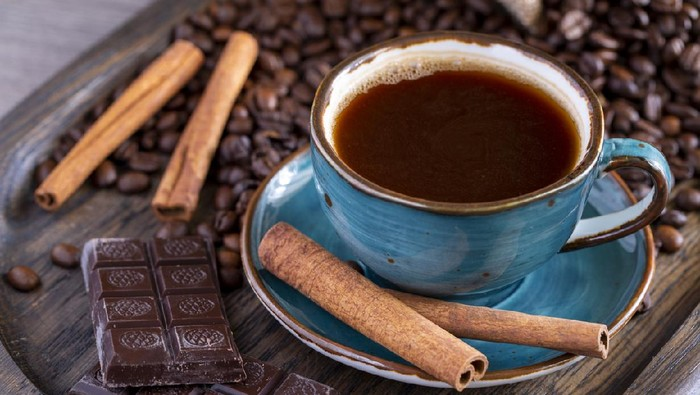 A cup of coffee, chocolate, cinnamon, coffee beans on a wooden tray. Life style. High quality photo