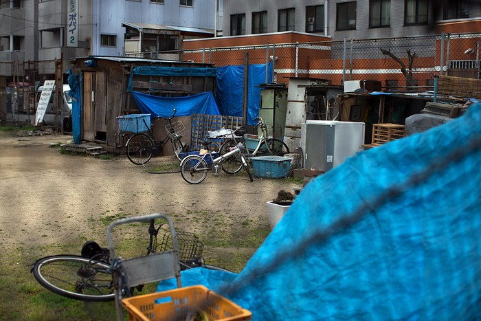 OSAKA, JAPAN - APRIL 24: A homeless woman pushes a wheelchair past the slum area of Kamagasaki on April 24, 2016 in Osaka, Japan. Kamagasaki, a district in Japan's second largest city Osaka, is home to around 25,000 day labourers, jobless and homeless most of whom start each day hoping for an offer of manual labour and end it queuing for a ticket to access the shelter.  (Photo by Carl Court/Getty Images)