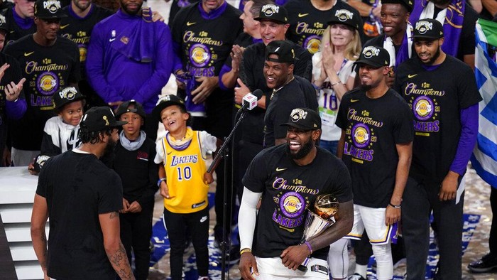 Los Angeles Lakers LeBron James (23) holds the trophy as he celebrates with his teammates after the Lakers defeated the Miami Heat 106-93 in Game 6 of basketballs NBA Finals Sunday, Oct. 11, 2020, in Lake Buena Vista, Fla. (AP Photo/Mark J. Terrill)