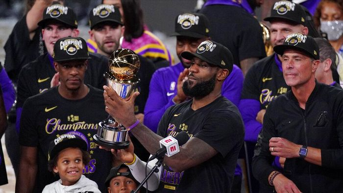 Los Angeles Lakers LeBron James (23) holds the MVP trophy as he celebrates with his teammates after the Lakers defeated the Miami Heat 106-93 in Game 6 of basketballs NBA Finals Sunday, Oct. 11, 2020, in Lake Buena Vista, Fla. (AP Photo/Mark J. Terrill)