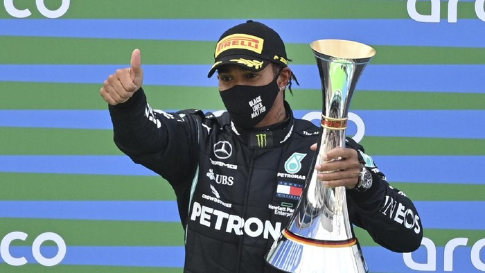 Mercedes driver Lewis Hamilton of Britain holds the trophy at the podium as he celebrates after winning the Eifel Formula One Grand Prix at the Nuerburgring racetrack in Nuerburg, Germany, Sunday, Oct. 11, 2020. (Ina Fassbender, Pool via AP)