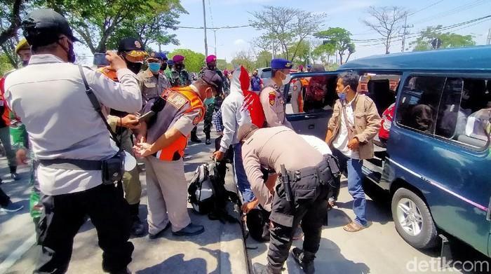 Petugas gabungan menggelar Operasi Yustisi  di Jembatan Suramadu sisi Surabaya. Selain operasi protokol kesehatan (prokes), razia ini juga untuk mengantisipasi aksi kejahatan.