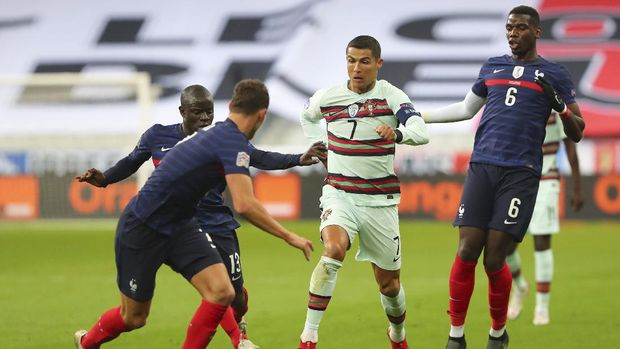 Portugal's Cristiano Ronaldo, center, runs with the ball at France's Benjamin Pavard, foreground, between Ngolo Kante and Paul Pogba, right, during the UEFA Nations League soccer match between France and Portugal at the Stade de France in Saint-Denis, north of Paris, France, Sunday, Oct. 11, 2020. (AP Photo/Thibault Camus)