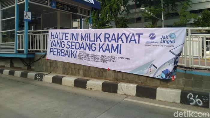 Spanduk yang bertuliskan HALTE INI MILIK RAKYAT YANG SEDANG KAMI PERBAIKI dan KAMI BERBENAH KARENA PENGALAMAN DAN PELAYANAN TERBAIK ADALAH HAK ANDA terpampang di Halte TransJakarta Sarinah, Jalan MH Thamrin, Jakarta Pusat, Senin (12/10/2020).