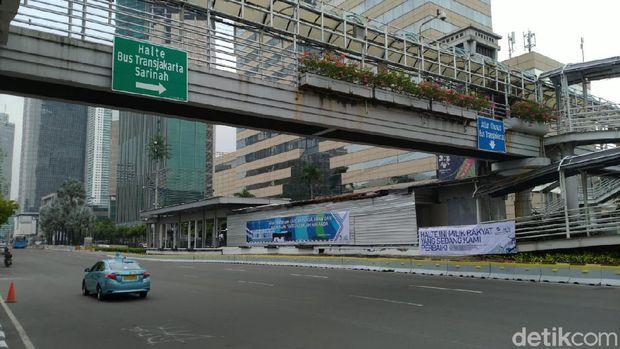 Spanduk yang bertuliskan 'HALTE INI MILIK RAKYAT YANG SEDANG KAMI PERBAIKI' dan 'KAMI BERBENAH KARENA PENGALAMAN DAN PELAYANAN TERBAIK ADALAH HAK ANDA' terpampang di Halte TransJakarta Sarinah, Jalan MH Thamrin, Jakarta Pusat, Senin (12/10/2020).