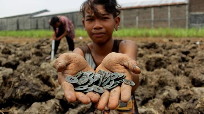 Warga menggali tanah mencari uang koin kuno yang tersebar di areal persawahan milik warga di Dusun Mojounggul, Kecamatan Bareng, Kabupaten Jombang, Senin (12/10/2020). Warga desa setempat ramai-ramai berburu koin kepeng atau mata uang kuno Cina untuk dijual ke pengepul dengan harga Rp.100 ribu perkilogramnya. ANTARA FOTO/Syaiful Arif/hp.