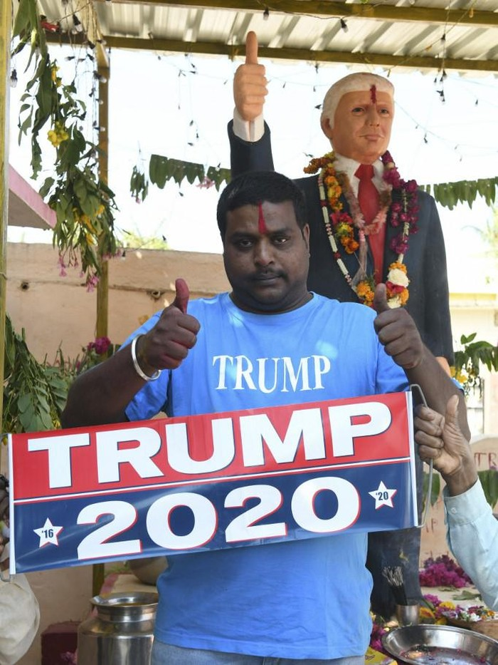 In this photo taken on February 17, 2020, farmer Bussa Krishna, 33, poses with a poster after offering prayers to the statue of US President Donald Trump, at his residence in Jangaon district in Telangana state, some 120 kms from Hyderabad, ahead of the visit of US President Donald Trump to India. - Die-hard Donald Trump fan Bussa Krishna is celebrating the visit of his hero to India next week the only way he knows how -- offering prayers to a life-sized idol of the US President in his home. (Photo by NOAH SEELAM / AFP) / To go with US-INDIA-POLITICS-DIPLOMACY-TRUMP-OFFBEAT