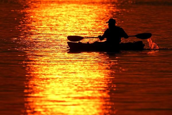 Seorang pria melintasi pantulan matahari terbenam saat berperahu di Danau Shawnee Mission, Kansas.
