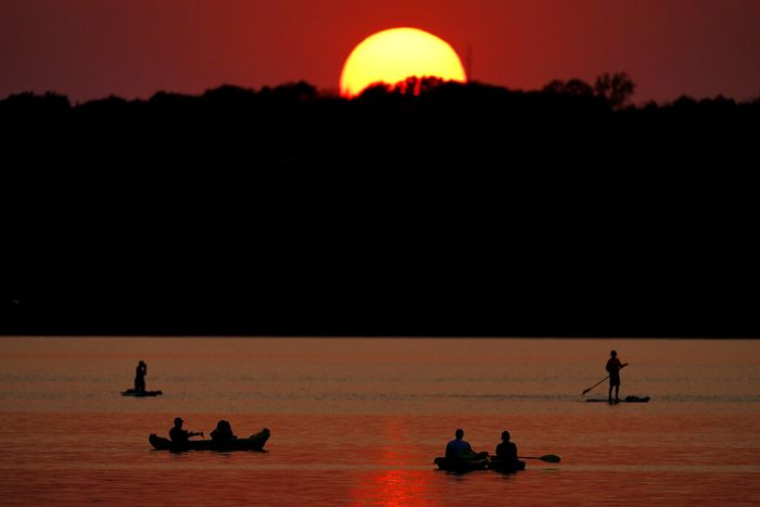 People watch the sunset while boating on Shawnee Mission Lake, Friday, Oct. 9, 2020, in Shawnee, Kan. Sunsets continue to be more vibrant than usual as smoke from western wildfires continue to drift across the country. (AP Photo/Charlie Riedel)
