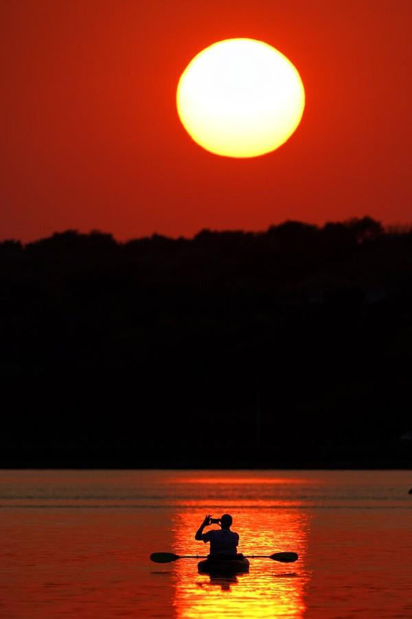 Seorang pria mengambil foto matahari terbenam saat berperahu di Danau Shawnee Mission, Kansas.