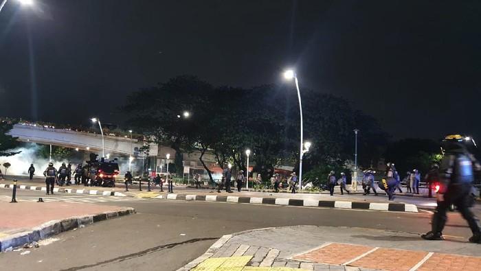 Massa perusuh yang didominasi remaja melempar petasan ke arah polisi di Jalan Jatibaru Raya, yang dibalas polisi dengan tembakan gas air mata.
