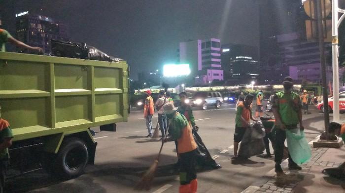 Petugas dari Dinas Lingkungan Hidup Jakarta Pusat membersihkan sisa sampah demonstrasi di Tugu Tani, Jakarta Pusat.