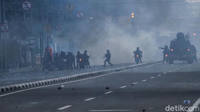 Massa berlarian usai dibubarkan pasukan Brimob dengan menggunakan gas air mata di Gambir, Jakarta, Selasa (13/10/2020).