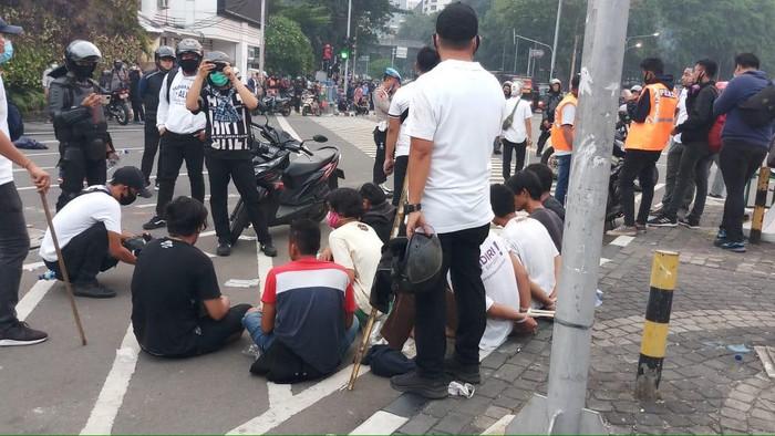 Polisi mengamankan belasan remaja di Tugu Tani yang diduga merusuh saat demo.
