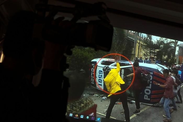 Petugas Kepolisian memperlihatkan rekaman video pengujukrasa yang melakukan pengrusakan kendaraan dinas Kepolisian saat unjukrasa tolak UU Cipta Kerja ketika gelar kasus, di Mapolda Riau, di Pekanbaru, Senin (12/10/2020). Pelaku yang saat berunjukrasa tolak UU Cipta Kerja pada Kamis (8/10/2020) lalu yang mengenakan jas almamater Universitas Lancang Kuning ini ternyata bukan lah seorang mahasiswa, Polisi juga memperlihatkan barang bukti pengrusakan berupa video rekaman, kayu, batu dan botol minuman keras. ANTARA FOTO/Rony Muharrman/hp.