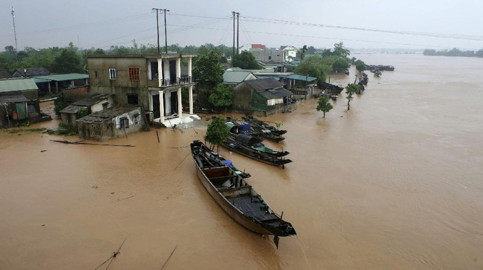Rescue workers travel by boat on a swelling river to access a flooded area in Quang Binh province, Vietnam, Monday, Oct. 12, 2020. Vietnam, Monday, Oct. 12, 2020. Torrential rains have flooded central Vietnam since last week as the region braces for more heavy rainfall. (Nguyen Van Ty/VNA via AP)
