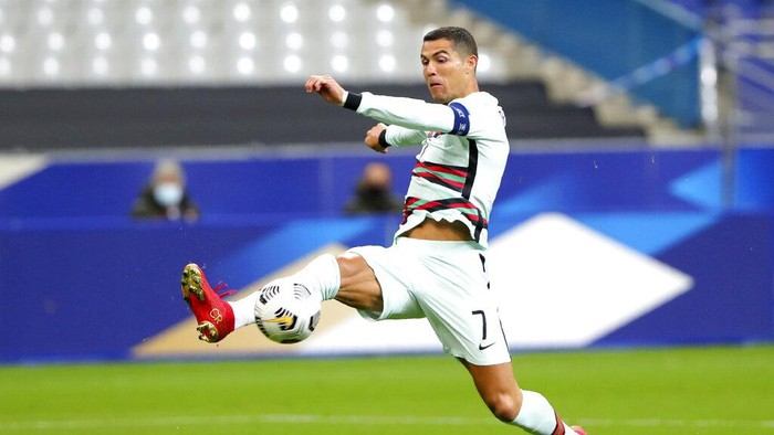 FILE - In this Sunday, Oct. 11, 2020 file photo Portugals Cristiano Ronaldo stretches for the ball during the UEFA Nations League soccer match between France and Portugal at the Stade de France in Saint-Denis, north of Paris, France. The Portuguese soccer federation says Cristiano Ronaldo has tested positive for the coronavirus. The federation says Ronaldo is doing well and has no symptoms. He has been dropped from the countrys Nations League match against Sweden on Wednesday. (AP Photo/Thibault Camus, File)