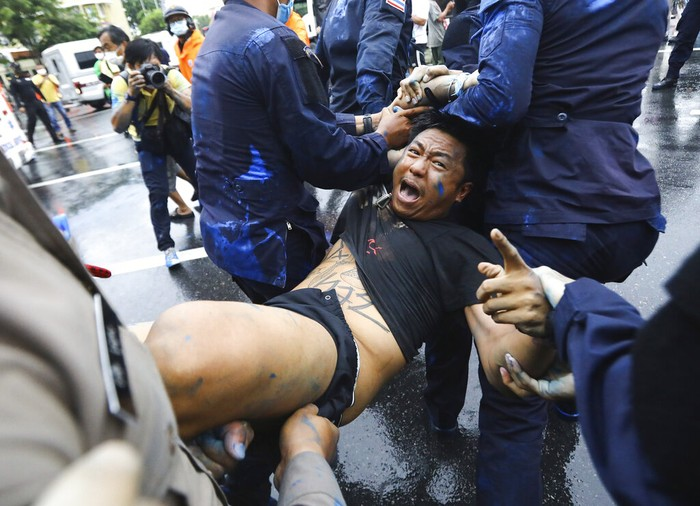 Police arrest activist Jatupat Boonpattararaksa near the Democracy Monument in Bangkok, Thailand, Tuesday, Oct. 13, 2020. Police have arrested several political activists who were planning to camp out a day early at the site of an anti-government rally scheduled for Wednesday. (AP Photo)