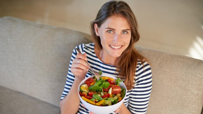 Shot of a young woman eating a bowl full of salad on her sofa at home