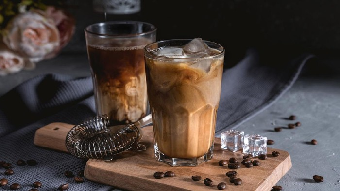 Iced coffee in a tall glass with cream on dark background