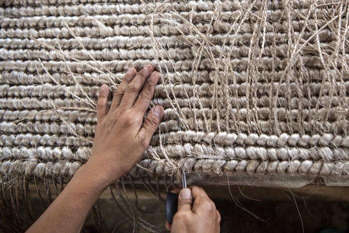 Djunaedi (71) pemilik CV Natural menunjukkan serat pohon pisang (abaca fiber) yang belum dipintal menjadi benang di bengkel anyam miliknya.
