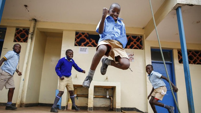 Schoolchildren joke around and play at the Olympic Primary School in Kibera, one of the capital Nairobi's poorest areas, in Kenya Monday, Oct. 12, 2020. Kenya partially re-opened schools on Monday to allow those students due for examinations which had been postponed to prepare, following a total closure of all educational institutions enacted since March to curb the spread of the coronavirus pandemic. (AP Photo/Brian Inganga)