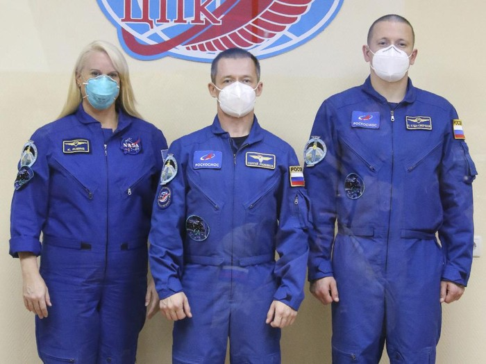 In this handout photo released by Roscosmos, U.S. astronaut Kate Rubins, left, Russian cosmonauts Sergey Ryzhikov, center, and Sergey Kud-Sverchkov, members of the main crew to the International Space Station (ISS), pose for a picture during a news conference at the Baikonur Cosmodrome, Kazakhstan, Tuesday, Oct. 13, 2020. The new Soyuz mission to the International Space Station is scheduled on Wednesday, Oct. 14. (Roscosmos Space Agency Press Service via AP)