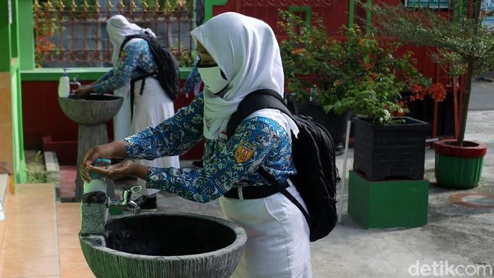 Guru melakukan pengecekan suhu tubuh pada Siswa-siswi Sekolah Menengah Pertama Negeri 1 Gantiwarno, Klaten, saat memasuki area sekolah pada saat uji coba sekolah tatap muka dengan standar protokol kesehatan ketat di Gantiwarno, Klaten, Jawa Tengah.