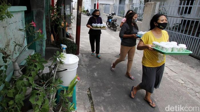 Sejumlah warga Gandekan, Surakarta, bergotong-royong memasak makanan bergizi untuk pasien OTG Corona yang sedang menjalani isolasi mandiri.