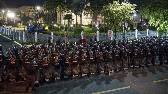 Pro-democracy protesters push Thai policemen with riot shields during a demonstration in Bangkok, Thailand, Thursday, Oct. 15, 2020. Thai police dispersed a group of protesters holding an overnight rally outside the prime ministers office. (AP Photo/Rapeephat Sitichailapa)