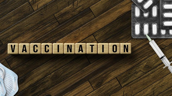 cubes with message VACCINATION and with syringe, face masks and pills on wooden background. (123rf/ fotogestoeber )