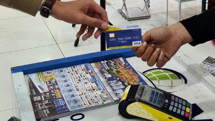 """Seorang petugas kasir sedang melayani pembayaran melalui Electronic Data Capture (EDC) salah satu pelanggan usai berbelanja di Mitra 10, di Jakarta, Kamis (15/10).  PT Bank Tabungan Negara (Persero) Tbk bekerjasama dengan """"Mitra 10"""" toko ritel bahan bangunan milik PT Catur Mitra Sejati Sentosa,  dengan menempatkan mesin EDC BTN di 35 Outlet Mitra 10 di seluruh Indonesia.  Bank BTN bersama Mitra 10 menggelar program undian berhadiah bertajuk """"End Year Vaganza"""" yang berlangsung sejak tanggal  1 Oktober dan akan berakhir pada  31 Desember 2020."""