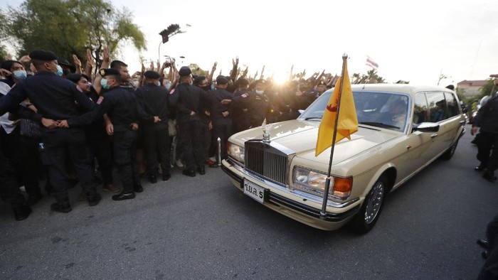 A vehicle with members of the Thai royal family onboard passes through a road where anti-government protesters gathered outside the Government House on Wednesday, Oct. 14, 2020 in Bangkok, Thailand. (AP Photo)