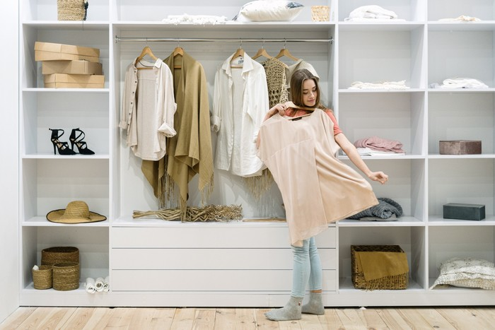 Young adult woman standing near modern wardrobe at home with contemporary interior, choosing trendy clothes, having difficult choice not knowing what to put on, trying on fashionable wear