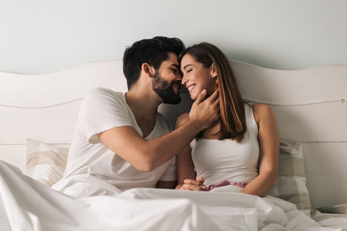 Affectionate young couple relaxing in bed and having a romantic moment