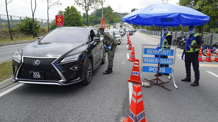 Police officers check vehicles at a roadblock to ensure that people abide by a movement control order on the outskirts of Kuala Lumpur, Malaysia, Wednesday, Oct. 14, 2020. Malaysia will restrict movements in its biggest city Kuala Lumpur, neighboring Selangor state and the administrative capital of Putrajaya from Wednesday to curb a sharp rise in coronavirus cases. (AP Photo/Vincent Thian)
