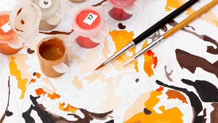 Female hand coloring paint by numbers picture. Creative hobby. Leisure activity at home during self-isolation COVID-19