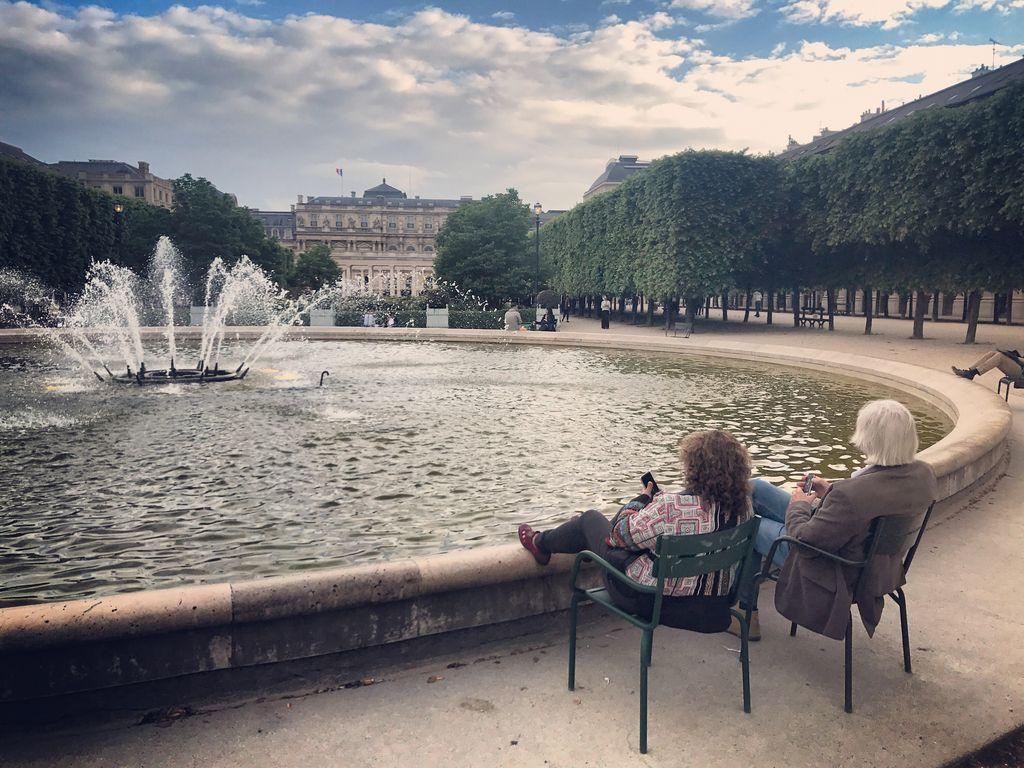 Warga bersantai dan menikmati sore yang hangat di Paris Jardin du Palais-Royal