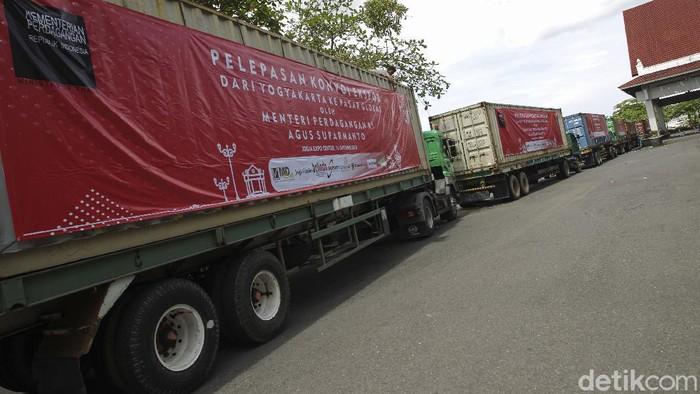 Karyawan memasang spanduk di atas truk kontainer berisi komoditas ekspor saat menunggu pelepasan konvoi Ekspor oleh Menteri Perdagangan di Jogja Expo Center, Yogyakarta, Jumat (16/10/2020). Sebanyak tujuh kontainer berisi produk kerajinan tangan dan komoditas ekspor lainnya menunggu pemberangkatan menuju pelabuhan Tanjung Emas Semarang, Jawa Tengah. Salah satu tujuan ekspor kali ini adalah kawasan Eropa. Pelepasan ekspor ini menjadi angin segar bagi industri kerajinan di Yogyakarta di tengah masa pandemi Covid-19. detikcom/Pius Erlangga