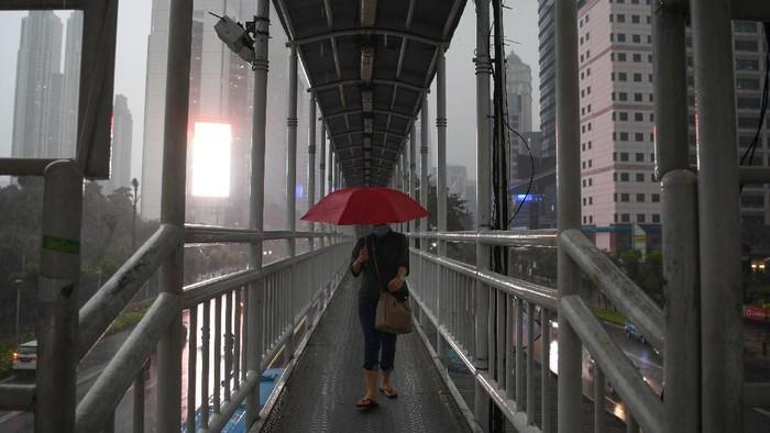 Seorang warga mengenakan jas hujan saat melintas di jembatan penyeberangan orang (JPO) di Senayan, Jakarta, Jumat (16/10/2020). Menurut Badan Meteorologi, Klimatologi dan Geofisika (BMKG) musim hujan di Indonesia telah berlangsung dari bulan Oktober dan diprediksi puncak musim hujan terjadi pada Januari hingga Februari 2021. ANTARA FOTO/Wahyu Putro A/wsj.